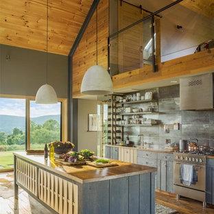 バーリントンの中サイズのモダンスタイルのおしゃれなキッチン (アンダーカウンターシンク、フラットパネル扉のキャビネット、グレーのキャビネット、木材カウンター、グレーのキッチンパネル、磁器タイルのキッチンパネル、シルバーの調理設備、無垢フローリング、茶色い床) の写真