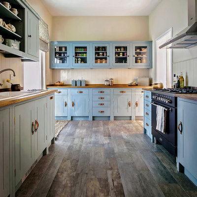 Example of a classic galley medium tone wood floor and brown floor enclosed kitchen design in London with a drop-in sink, shaker cabinets, blue cabinets, wood countertops, beige backsplash, black appliances and no island