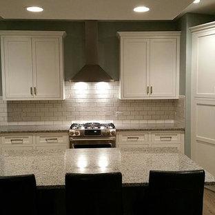 シカゴの大きいトランジショナルスタイルのおしゃれなキッチン (ドロップインシンク、フラットパネル扉のキャビネット、黄色いキャビネット、御影石カウンター、白いキッチンパネル、セラミックタイルのキッチンパネル、シルバーの調理設備の、無垢フローリング) の写真