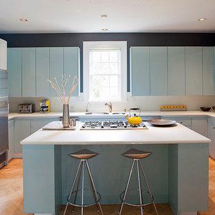 Idées déco pour une cuisine exotique en U avec un évier 2 bacs, un placard à porte plane, des portes de placard bleues et un électroménager en acier inoxydable.