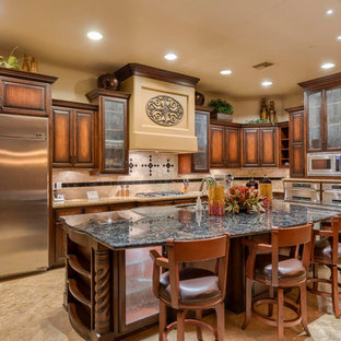 Southwestern kitchen appliance - Example of a southwest l-shaped beige floor kitchen design in Phoenix with an undermount sink, raised-panel cabinets, medium tone wood cabinets, multicolored backsplash, stainless steel appliances and an island