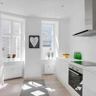 Foto di una cucina parallela scandinava di medie dimensioni con lavello sottopiano, ante lisce, ante bianche, elettrodomestici in acciaio inossidabile, parquet chiaro, nessuna isola e top in laminato