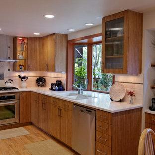 ポートランドの中サイズのアジアンスタイルのおしゃれなキッチン (ドロップインシンク、フラットパネル扉のキャビネット、中間色木目調キャビネット、クオーツストーンカウンター、白いキッチンパネル、サブウェイタイルのキッチンパネル、シルバーの調理設備、淡色無垢フローリング、アイランドなし) の写真
