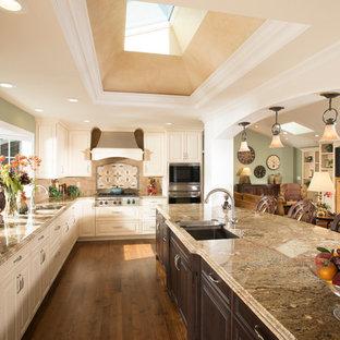 Diseño de cocina en L, clásica, extra grande, abierta, con fregadero bajoencimera, armarios con paneles con relieve, puertas de armario beige, encimera de granito, salpicadero multicolor, electrodomésticos de acero inoxidable y una isla