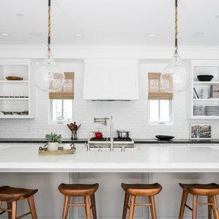 Foto de cocina en U, costera, con armarios abiertos, puertas de armario blancas, salpicadero blanco, salpicadero de ladrillos, electrodomésticos de acero inoxidable, suelo de madera oscura y una isla