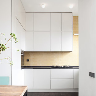 Esempio di una grande cucina abitabile minimalista con ante lisce, ante bianche, top in quarzite, paraspruzzi beige, paraspruzzi con piastrelle in ceramica, elettrodomestici in acciaio inossidabile, parquet scuro e nessuna isola