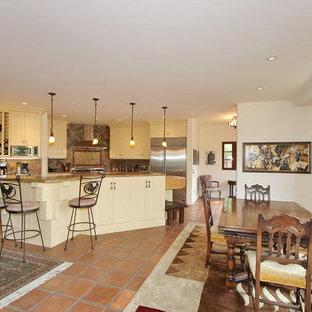 Inspiration för ett stort medelhavsstil kök, med en undermonterad diskho, luckor med profilerade fronter, gula skåp, granitbänkskiva, grått stänkskydd, stänkskydd i stenkakel, rostfria vitvaror, klinkergolv i terrakotta och en köksö