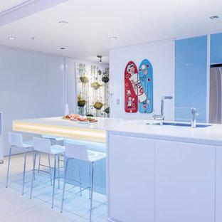 Große Moderne Wohnküche in L-Form mit Doppelwaschbecken, Glasfronten, blauen Schränken, Mineralwerkstoff-Arbeitsplatte, Küchenrückwand in Blau, Glasrückwand, Küchengeräten aus Edelstahl, Porzellan-Bodenfliesen und Kücheninsel in Auckland
