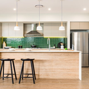 Photo of a contemporary galley kitchen in Sydney with flat-panel cabinets, light wood cabinets, green splashback, mosaic tile splashback, stainless steel appliances, with island, beige floor and white benchtop.
