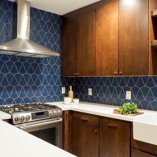 Photo of a small contemporary u-shaped separate kitchen in San Francisco with a farmhouse sink, flat-panel cabinets, dark wood cabinets, blue splashback, ceramic splashback, stainless steel appliances, ceramic floors, a peninsula, beige floor and white benchtop.