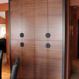 カルガリーの中サイズのアジアンスタイルのおしゃれなキッチン (アンダーカウンターシンク、フラットパネル扉のキャビネット、濃色木目調キャビネット、御影石カウンター、黒いキッチンパネル、石スラブのキッチンパネル、黒い調理設備、セラミックタイルの床) の写真