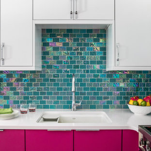 Bild på ett mellanstort funkis vit vitt kök, med släta luckor, bänkskiva i kvartsit, stänkskydd med metallisk yta, rostfria vitvaror, en enkel diskho, vita skåp och stänkskydd i tunnelbanekakel