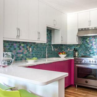 ボストンの中サイズのコンテンポラリースタイルのおしゃれなキッチン (アンダーカウンターシンク、フラットパネル扉のキャビネット、赤いキャビネット、珪岩カウンター、メタリックのキッチンパネル、ガラスタイルのキッチンパネル、シルバーの調理設備の、無垢フローリング、茶色い床、白いキッチンカウンター) の写真