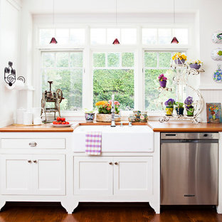Mid-sized shabby-chic style l-shaped kitchen in Los Angeles with a farmhouse sink, shaker cabinets, white cabinets, wood benchtops, white splashback, stainless steel appliances, medium hardwood floors and with island.