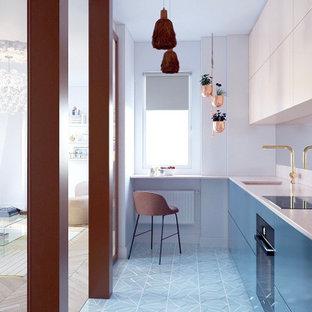 Modern inredning av ett avskilt, mellanstort beige beige l-kök, med en integrerad diskho, släta luckor, bänkskiva i kalksten, stänkskydd med metallisk yta, spegel som stänkskydd, cementgolv och turkost golv