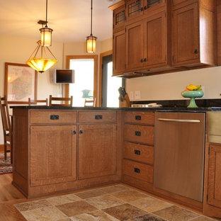 Immagine di una cucina stile americano di medie dimensioni con lavello stile country, ante lisce, ante marroni, top in granito, paraspruzzi nero, elettrodomestici in acciaio inossidabile, pavimento in pietra calcarea, pavimento beige e top nero