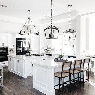 Klassische Küche mit Unterbauwaschbecken, weißen Schränken, Quarzwerkstein-Arbeitsplatte, Küchenrückwand in Schwarz, Rückwand aus Marmor, schwarzen Elektrogeräten, braunem Holzboden, zwei Kücheninseln, braunem Boden und weißer Arbeitsplatte in Phoenix