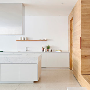 Design ideas for a large contemporary galley kitchen pantry in Melbourne with an undermount sink, marble benchtops, white splashback, stone tile splashback, concrete floors, with island, white floor, white benchtop, flat-panel cabinets and white cabinets.