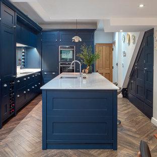 Inredning av ett klassiskt vit vitt kök och matrum, med en undermonterad diskho, skåp i shakerstil, blå skåp, svarta vitvaror, en köksö, brunt golv och mörkt trägolv