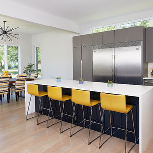 Mid-sized modern l-shaped eat-in kitchen in Grand Rapids with an integrated sink, flat-panel cabinets, grey cabinets, quartz benchtops, white splashback, stone tile splashback, stainless steel appliances, bamboo floors and with island.