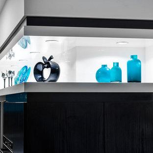 Immagine di una cucina design di medie dimensioni con lavello sottopiano, ante lisce, ante turchesi, top in quarzo composito, elettrodomestici neri, pavimento in legno massello medio e isola