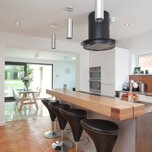 Medium sized contemporary galley kitchen/diner in Oxfordshire with flat-panel cabinets, white cabinets, stainless steel worktops, stainless steel appliances, medium hardwood flooring, an island, brown floors and brown splashback.