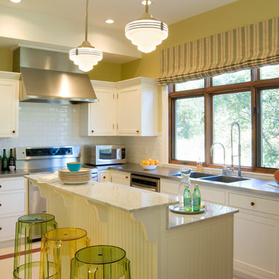 Inspiration for a timeless l-shaped kitchen remodel in Denver with a double-bowl sink, shaker cabinets, white cabinets, white backsplash, subway tile backsplash, stainless steel appliances and an island