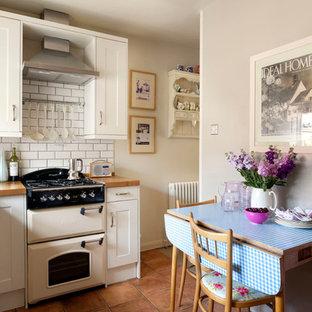 サリーのヴィクトリアン調のおしゃれなダイニングキッチン (落し込みパネル扉のキャビネット、白いキャビネット、木材カウンター、白いキッチンパネル、サブウェイタイルのキッチンパネル、白い調理設備) の写真