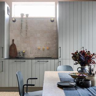 ロンドンのインダストリアルスタイルのおしゃれなダイニングキッチン (グレーのキャビネット、ライムストーンカウンター、コンクリートの床、グレーの床、黒いキッチンカウンター、シングルシンク、ピンクのキッチンパネル) の写真