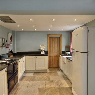 This is an example of a large victorian l-shaped separate kitchen in Other with a farmhouse sink, beaded inset cabinets, beige cabinets, black splashback, slate splashback, coloured appliances, slate floors and beige floor.