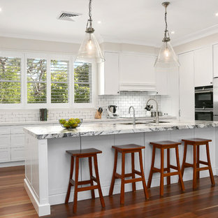 Inspiration for a transitional u-shaped kitchen in Newcastle - Maitland with an undermount sink, shaker cabinets, white cabinets, white splashback, subway tile splashback, stainless steel appliances, medium hardwood floors, with island, brown floor and white benchtop.
