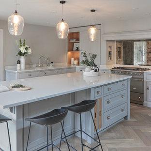 ハートフォードシャーのトランジショナルスタイルのおしゃれなアイランドキッチン (シェーカースタイル扉のキャビネット、グレーのキャビネット、ミラータイルのキッチンパネル、シルバーの調理設備の、淡色無垢フローリング、茶色い床、白いキッチンカウンター) の写真