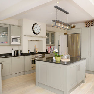 Design ideas for a traditional eat-in kitchen in London with a double-bowl sink, shaker cabinets, grey cabinets, stainless steel appliances, light hardwood floors, with island and granite benchtops.