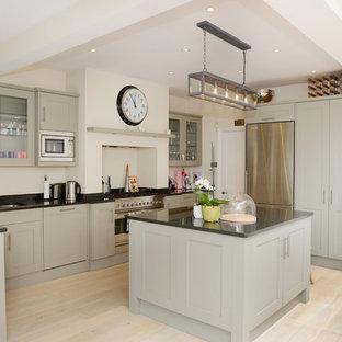 ロンドンのヴィクトリアン調のおしゃれなキッチン (ダブルシンク、シェーカースタイル扉のキャビネット、グレーのキャビネット、シルバーの調理設備の、淡色無垢フローリング、御影石カウンター) の写真