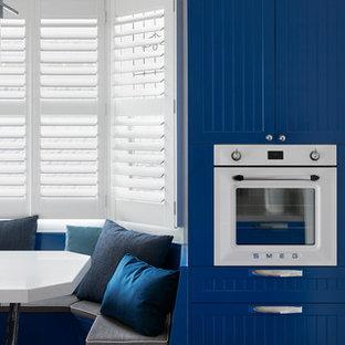 Einzeilige, Große Retro Küche mit Vorratsschrank, Waschbecken, Kassettenfronten, blauen Schränken, Edelstahl-Arbeitsplatte, Küchengeräten aus Edelstahl, braunem Holzboden und Kücheninsel in Melbourne
