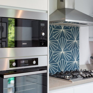 Inspiration for a mid-sized transitional l-shaped eat-in kitchen in London with limestone benchtops, blue splashback, cement tile splashback, painted wood floors, no island, white floor and beige benchtop.