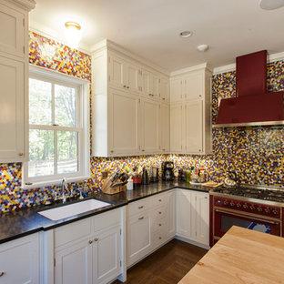 ニューヨークの中くらいのヴィクトリアン調のおしゃれなキッチン (アンダーカウンターシンク、フラットパネル扉のキャビネット、白いキャビネット、御影石カウンター、マルチカラーのキッチンパネル、セラミックタイルのキッチンパネル、カラー調理設備、無垢フローリング) の写真