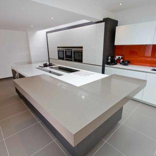 ウエストミッドランズの巨大なコンテンポラリースタイルのおしゃれなキッチン (一体型シンク、フラットパネル扉のキャビネット、白いキャビネット、オレンジのキッチンパネル、ガラス板のキッチンパネル、セラミックタイルの床) の写真