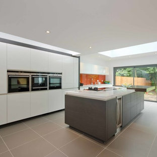 Contemporary enclosed kitchen ideas - Trendy single-wall ceramic floor enclosed kitchen photo in West Midlands with flat-panel cabinets, orange backsplash, glass sheet backsplash, an island, an integrated sink and white appliances