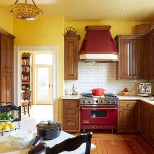 サンフランシスコの中サイズのヴィクトリアン調のおしゃれなキッチン (ダブルシンク、レイズドパネル扉のキャビネット、濃色木目調キャビネット、大理石カウンター、白いキッチンパネル、セラミックタイルのキッチンパネル、カラー調理設備、無垢フローリング、アイランドなし、茶色い床) の写真