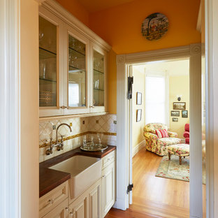 Mid-sized victorian enclosed kitchen designs - Inspiration for a mid-sized victorian l-shaped medium tone wood floor and brown floor enclosed kitchen remodel in San Francisco with a double-bowl sink, raised-panel cabinets, dark wood cabinets, marble countertops, white backsplash, ceramic backsplash, colored appliances and no island