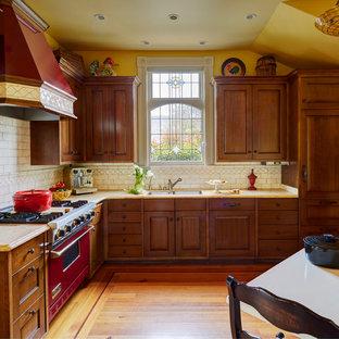 Idées déco pour une cuisine américaine victorienne en L de taille moyenne avec un évier 2 bacs, un placard avec porte à panneau surélevé, un plan de travail en marbre, une crédence blanche, une crédence en carreau de céramique, un électroménager de couleur, un sol en bois brun, aucun îlot, des portes de placard en bois brun et un sol orange.