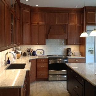Klassisk inredning av ett avskilt, stort l-kök, med en undermonterad diskho, skåp i shakerstil, skåp i mellenmörkt trä, granitbänkskiva, vitt stänkskydd, stänkskydd i keramik, rostfria vitvaror, vinylgolv, en köksö och gult golv