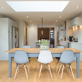This is an example of a contemporary galley eat-in kitchen in Surrey with flat-panel cabinets, grey cabinets, stainless steel appliances, light hardwood floors, with island, an integrated sink, solid surface benchtops, grey splashback and glass sheet splashback.