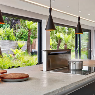 Photo of a large contemporary galley open plan kitchen in Devon with flat-panel cabinets, grey cabinets, concrete benchtops, stainless steel appliances, light hardwood floors, with island, multi-coloured floor and grey benchtop.