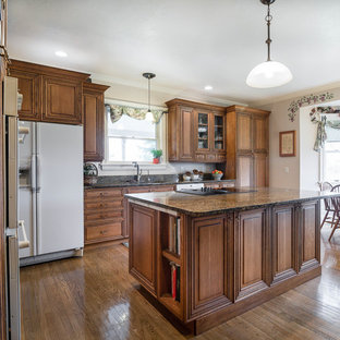 Victorian l-shaped kitchen in Salt Lake City with a submerged sink, raised-panel cabinets, medium wood cabinets, granite worktops, white appliances, medium hardwood flooring, an island and multicoloured worktops.