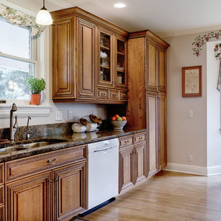 Photo of a victorian l-shaped kitchen in Salt Lake City with a submerged sink, raised-panel cabinets, medium wood cabinets, granite worktops, white appliances, medium hardwood flooring, an island and multicoloured worktops.