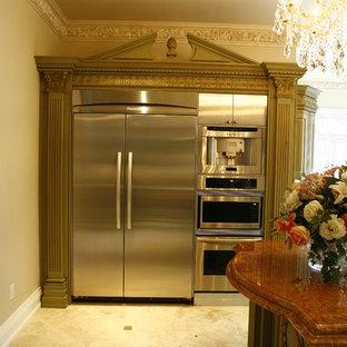 ダラスの中サイズのトラディショナルスタイルのおしゃれなキッチン (ダブルシンク、レイズドパネル扉のキャビネット、緑のキャビネット、大理石カウンター、ベージュキッチンパネル、石タイルのキッチンパネル、シルバーの調理設備の、トラバーチンの床) の写真