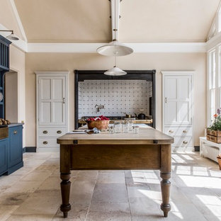 This is an example of a large classic l-shaped enclosed kitchen in London with a belfast sink, recessed-panel cabinets, blue cabinets, white splashback, porcelain splashback, integrated appliances, limestone flooring, an island, beige floors, wood worktops and brown worktops.