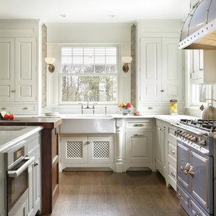 ニューヨークのヴィクトリアン調のおしゃれなL型キッチン (エプロンフロントシンク、レイズドパネル扉のキャビネット、白いキャビネット、白いキッチンパネル、サブウェイタイルのキッチンパネル、カラー調理設備) の写真